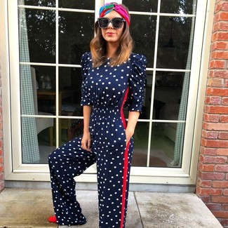 How to wear: navy polka dot jumpsuit, red suede pumps, black sunglasses, multi colored headband