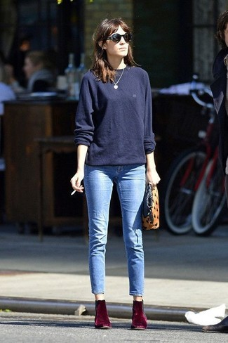 Alexa Chung wearing Navy Oversized Sweater, Light Blue Jeans, Burgundy Velvet Ankle Boots, Tan Suede Clutch