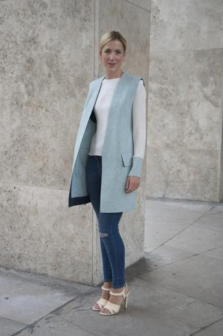 How to wear: beige leather heeled sandals, navy ripped skinny jeans, white long sleeve t-shirt, light blue sleeveless coat