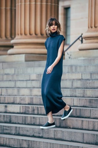 Wear a navy sweater dress to create a chic, glamorous look. A pair of black leather slip-on sneakers brings the dressed-down touch to the getup. A look like this makes it easy to embrace the colder months.
