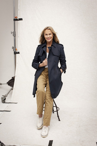 Lauren Hutton wearing Navy Trenchcoat, White Crew-neck T-shirt, Khaki Chinos, White Plimsolls