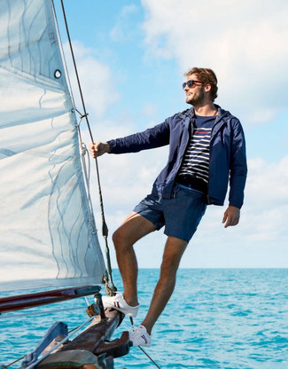 How to wear: navy windbreaker, navy and white horizontal striped crew-neck sweater, navy swim shorts, white canvas low top sneakers