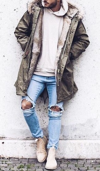 How to wear: olive parka, beige hoodie, light blue ripped skinny jeans, beige suede chelsea boots
