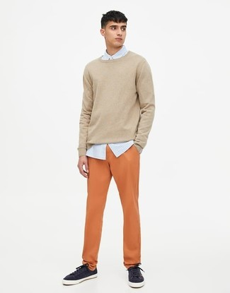 How to wear: navy low top sneakers, orange chinos, light blue vertical striped dress shirt, beige crew-neck sweater