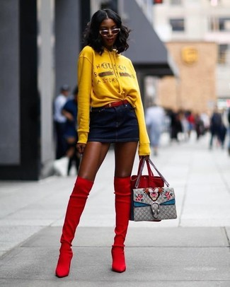 How to wear: red suede bucket bag, red suede over the knee boots, navy denim mini skirt, yellow print hoodie