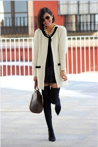 How to wear: dark brown print leather tote bag, black suede over the knee boots, black shift dress, white and black knit open cardigan