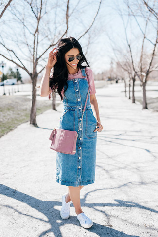 How to wear: blue denim overall dress, pink crew-neck t-shirt, white canvas low top sneakers, pink leather crossbody bag