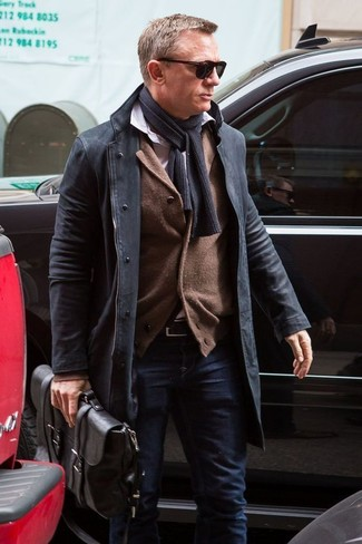 How to wear: black overcoat, brown cardigan, white long sleeve shirt, navy jeans