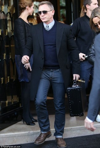 Daniel Craig wearing Black Overcoat, Navy V-neck Sweater, Grey Dress Shirt, Navy Jeans
