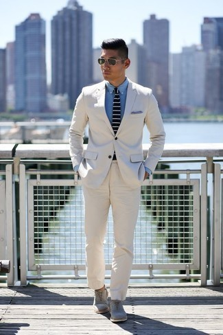 How to Wear a White Suit: Dress for success in a white suit and a light blue chambray dress shirt. Add a pair of grey suede oxford shoes to your outfit to tie the whole outfit together.