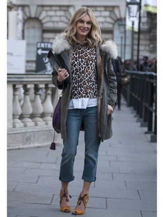 How to wear: charcoal parka, brown leopard crew-neck sweater, white dress shirt, blue jeans