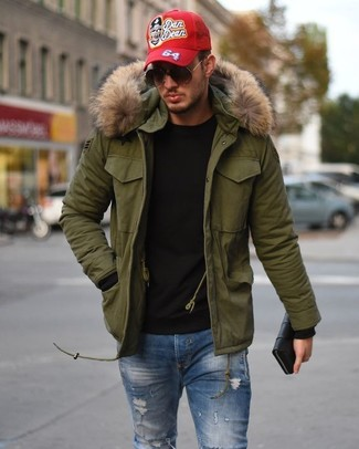 How to wear: olive parka, black crew-neck sweater, blue ripped skinny jeans, red print baseball cap