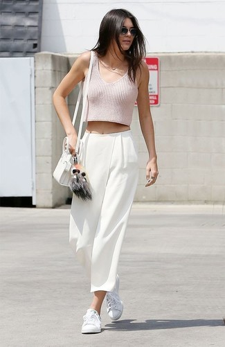 Kendall Jenner wearing Pink Cropped Top, White Wide Leg Pants, White Low Top Sneakers, White Leather Crossbody Bag