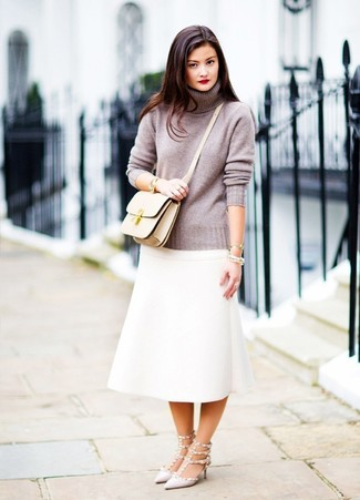 How to Wear a Beige Leather Crossbody Bag: A grey turtleneck and a beige leather crossbody bag are absolute staples that will integrate brilliantly within your daily casual wardrobe. You can get a bit experimental in the shoe department and introduce grey studded leather pumps to the mix.