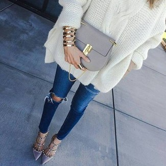 How to wear: grey leather crossbody bag, grey leather pumps, navy ripped skinny jeans, white knit oversized sweater