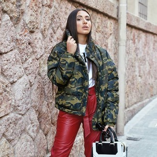 How to wear: white and black leather tote bag, red leather tapered pants, white and black print crew-neck t-shirt, olive camouflage puffer jacket