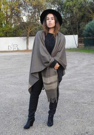 A dark grey knit oversized sweater and black leggings are great essentials to incorporate into your current wardrobe. Take a classic approach with the footwear and choose a pair of black leather knee high boots.