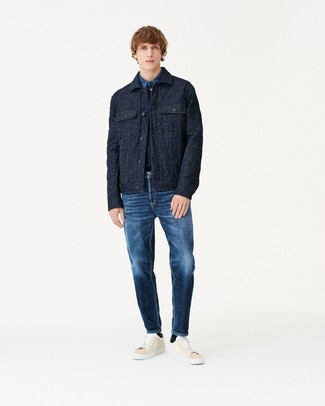 How to wear: navy quilted shirt jacket, blue denim shirt, navy jeans, beige leather low top sneakers