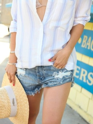 How to wear: khaki straw hat, blue ripped denim shorts, beige crochet bikini top, white and blue vertical striped dress shirt