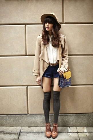 How to wear: brown leather lace-up ankle boots, navy denim shorts, white silk button down blouse, tan trenchcoat