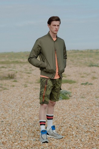 How to wear: grey suede low top sneakers, olive camouflage shorts, orange crew-neck sweater, olive bomber jacket