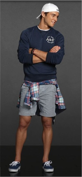 How to wear: navy low top sneakers, grey shorts, blue plaid long sleeve shirt, navy crew-neck sweater
