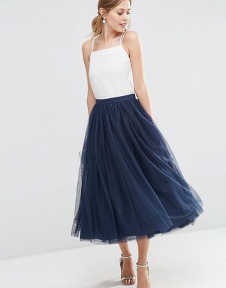How to Wear a Navy Full Skirt: This combo of a white silk tank and a navy full skirt looks chic and makes you look instantly cooler. Finishing off with a pair of silver leather heeled sandals is a surefire way to add a little flair to your getup.