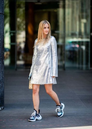 Get into glamour mode in a silver shift dress. Bring playfulness to your look with blue athletic shoes. As the weather starts to cool down, you'll see that a look like this is ideal for fall.