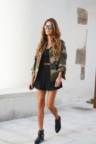 How to wear: black leather ankle boots, black skater skirt, black cropped top, olive camouflage military jacket
