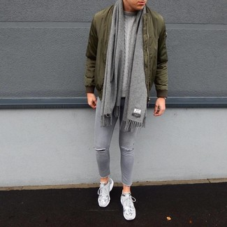 How to wear: grey athletic shoes, grey ripped skinny jeans, grey cable sweater, olive bomber jacket