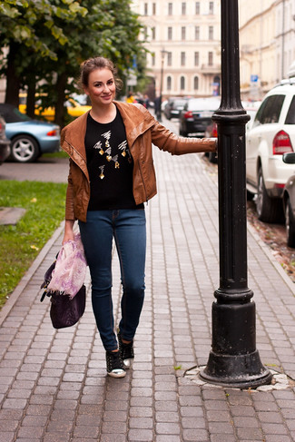 How to wear: black low top sneakers, navy skinny jeans, black embellished crew-neck sweater, tobacco leather biker jacket
