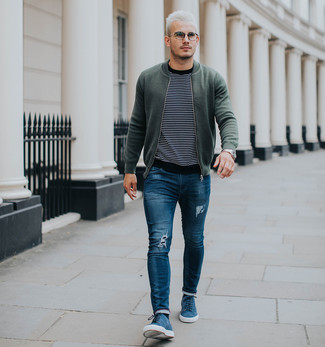 How to wear: blue suede low top sneakers, blue ripped skinny jeans, black and white horizontal striped crew-neck sweater, olive bomber jacket