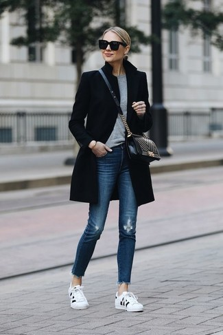 How to wear: white and black low top sneakers, blue ripped skinny jeans, grey crew-neck sweater, black coat