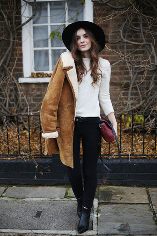 How to wear: black leather ankle boots, black skinny jeans, white crew-neck sweater, tan shearling coat