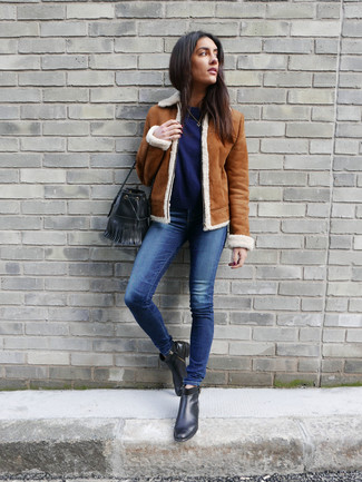 How to wear: black leather ankle boots, blue skinny jeans, navy crew-neck sweater, tobacco shearling jacket