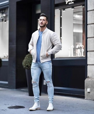 How to wear: white suede chelsea boots, light blue ripped skinny jeans, blue crew-neck t-shirt, beige bomber jacket