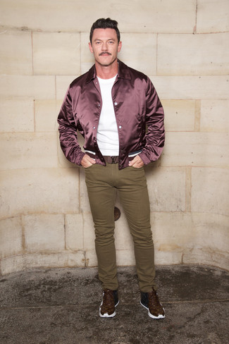 A burgundy bomber jacket and olive skinny jeans are a combination that every modern man should have in his closet. For something more on the daring side to complement your outfit, complement your outfit with a pair of dark brown print leather high top sneakers.