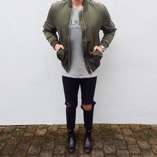 How to wear: black leather chelsea boots, black ripped skinny jeans, grey print crew-neck t-shirt, olive bomber jacket