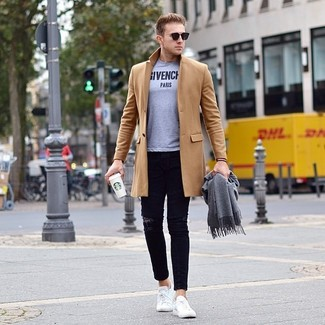 How to wear: white low top sneakers, black ripped skinny jeans, grey print crew-neck t-shirt, camel overcoat