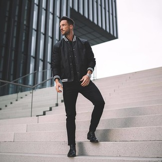 How to wear: black leather chelsea boots, black skinny jeans, black crew-neck t-shirt, black and white varsity jacket