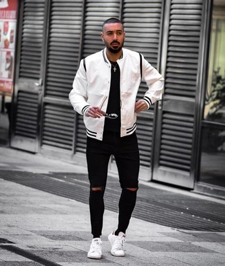 How to wear: white leather low top sneakers, black ripped skinny jeans, black crew-neck t-shirt, white and black varsity jacket