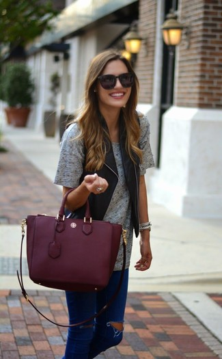 How to wear: burgundy leather tote bag, navy ripped skinny jeans, grey crew-neck t-shirt, black leather vest