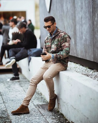 How to wear: brown suede dress boots, beige skinny jeans, blue denim shirt, olive camouflage military jacket