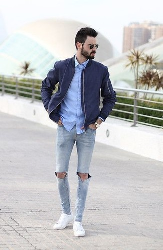 Which Bomber Jacket To Wear With a Light Blue Chambray Dress Shirt For Men: A bomber jacket and a light blue chambray dress shirt are the perfect base for a myriad of sharp outfits. Go the extra mile and jazz up your look by finishing off with white low top sneakers.