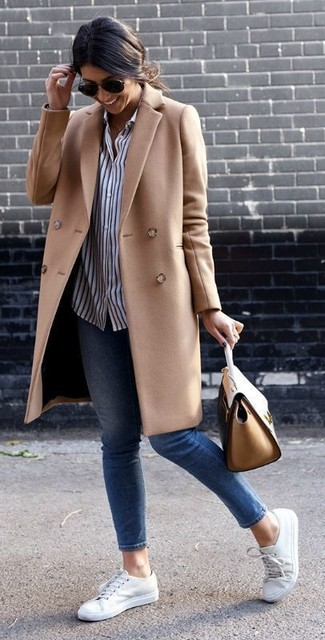 How to wear: white low top sneakers, blue skinny jeans, white and navy vertical striped dress shirt, camel coat