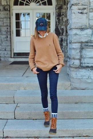 How to wear: tan snow boots, navy skinny jeans, white dress shirt, tan crew-neck sweater