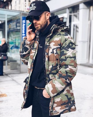How to wear: black and white print baseball cap, black skinny jeans, black hoodie, olive camouflage parka
