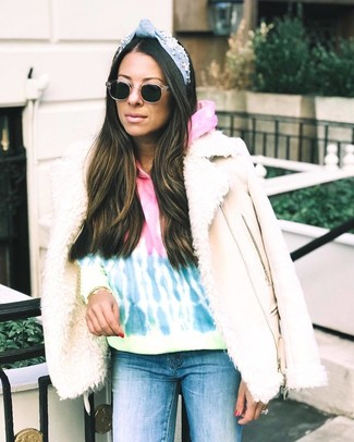 How to wear: black sunglasses, blue skinny jeans, multi colored tie-dye hoodie, beige shearling jacket
