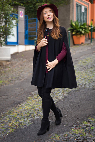 How to wear: black suede ankle boots, black skinny jeans, burgundy long sleeve blouse, black cape coat