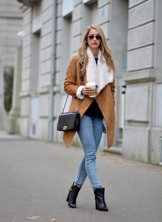 How to wear: black leather ankle boots, light blue skinny jeans, black long sleeve blouse, tan shearling coat